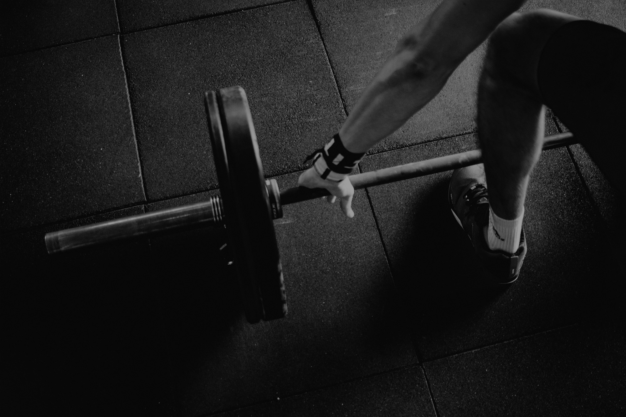 A young man in position to perform a deadlift exercise at the gym